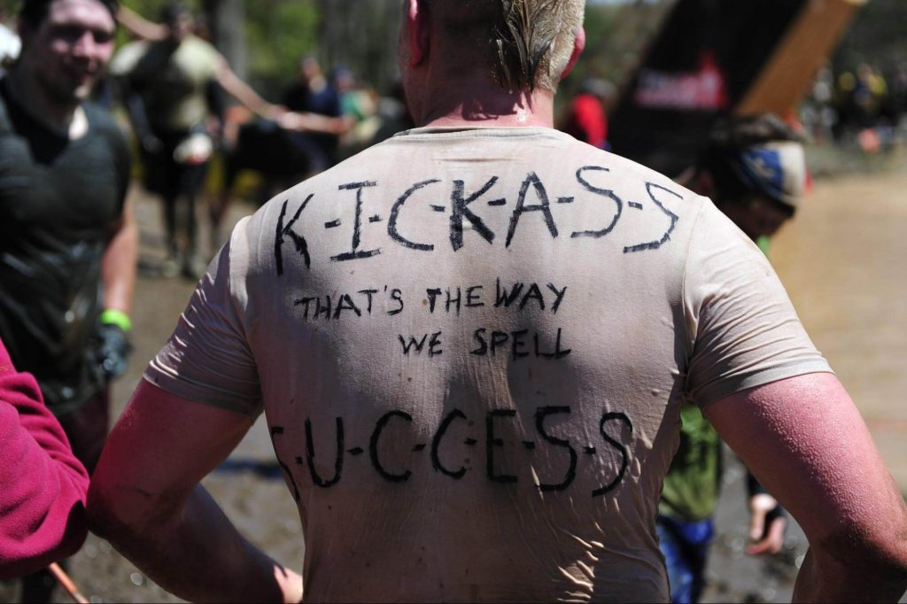 """Man running and wearing a T-shirt that has """"Kickass is the way we spell success"""" written on his back."""